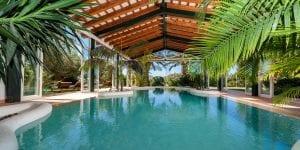 La Finca Ses Cuarterades cuenta con unos preciosos jardines y una increíble piscina rodeada de cristaleras y vegetación