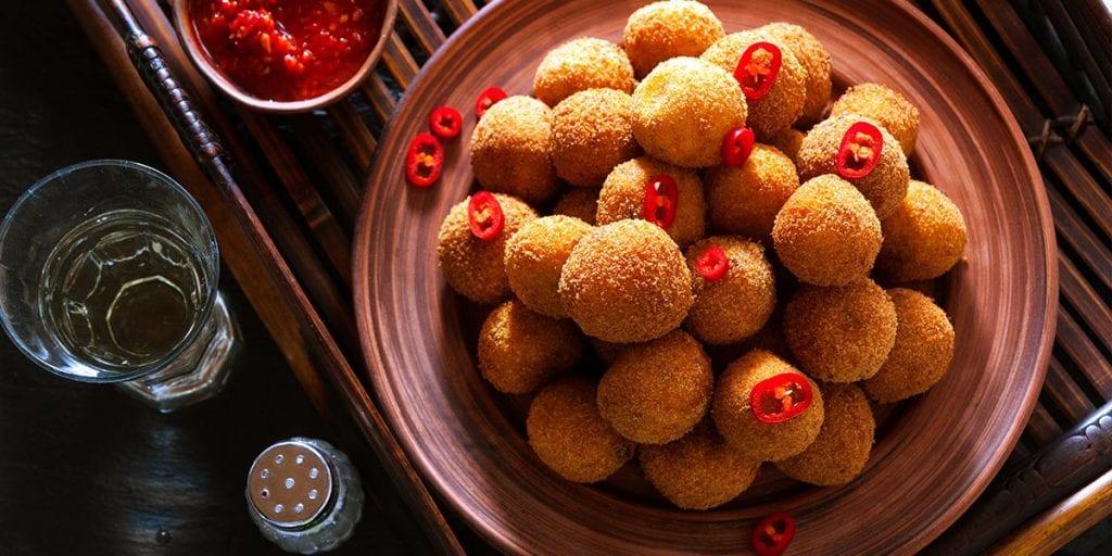 Los arancini son bolas de arroz, queso y azafrán rellenas y fritas que se toman como aperitivo caliente en Sicilia