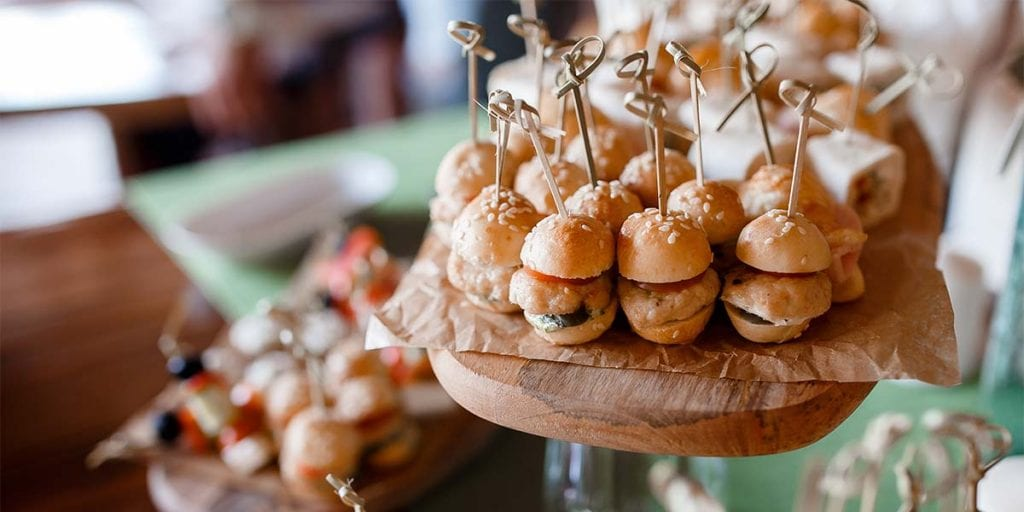 Grandes platos servidos en pequeño formato, como mini hamburguesas, mini pizzas, mini perritos calientes...