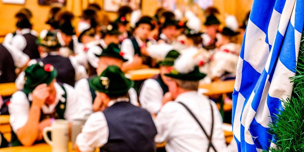 Coloca mesas largas y bancos de madera para que todos tus invitados se sienten cerca unos de otros